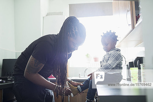 Father with long braids putting shoes on toddler son in sunny kitchen