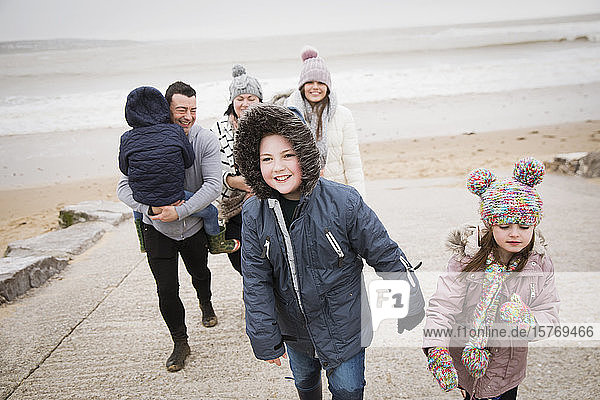Happy family in warm clothing walking up beach ramp
