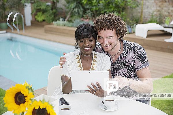Happy multiethnic couple using digital tablet at poolside patio