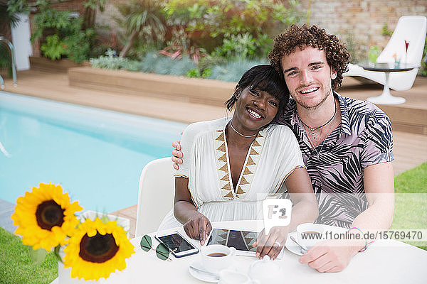 Portrait happy young multiethnic couple at poolside