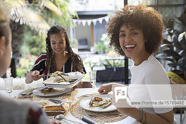 Portrait happy young woman eating lunch with friends at table