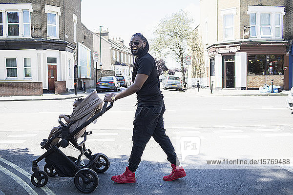 Portrait happy father pushing toddler son in stroller on sunny urban street