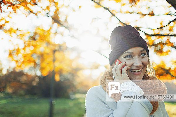 Young woman in stocking cap and scarf talking on smart phone in sunny autumn park
