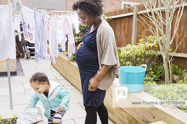 Pregnant mother and daughter hanging laundry on clothesline