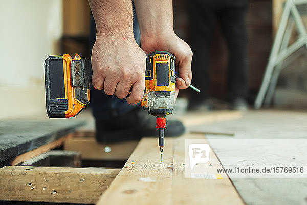 Close up construction worker using power drill installing floorboard