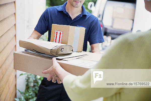 Deliveryman handing packages to woman at front door