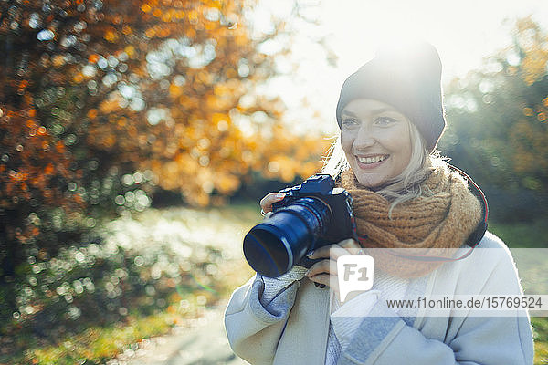 Smiling woman with digital camera in sunny autumn park