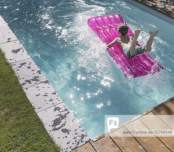 Playful boy jumping on inflatable raft in sunny summer swimming pool