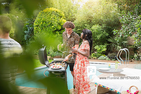 Young multiethnic couple barbecuing at summer poolside