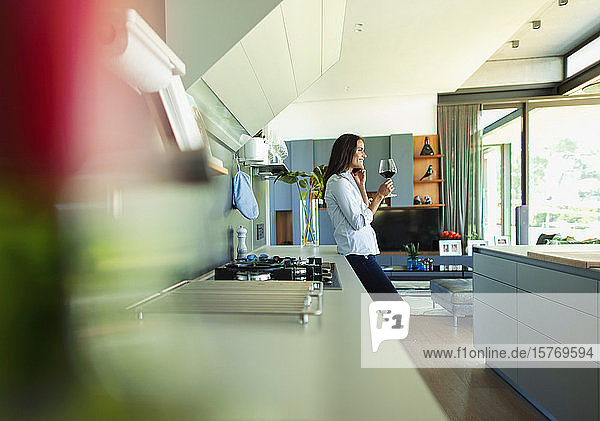 Woman drinking red wine and talking on smart phone in modern kitchen