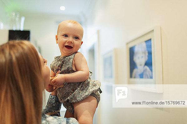 Mother holding happy cute baby girl in corridor