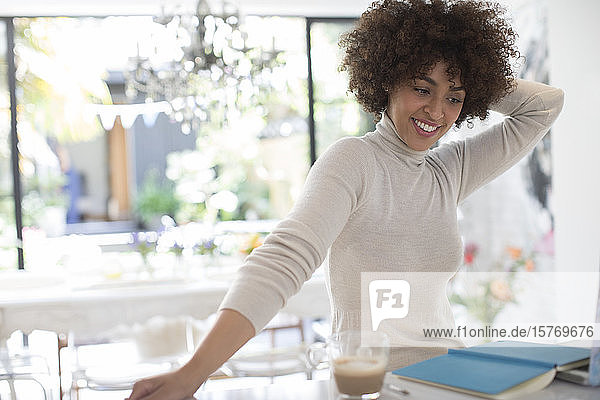 Happy young female freelancer working in kitchen