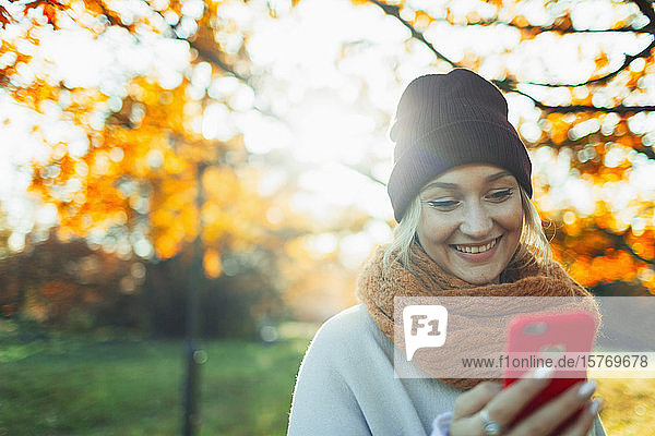 Smiling woman with smart phone in sunny autumn park