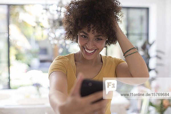 Confident smiling young woman taking selfie with camera phone