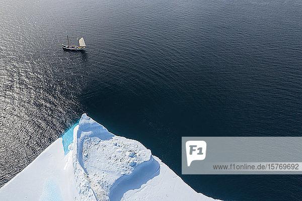 Ship sailing past iceberg on sunny Atlantic Ocean Greenland