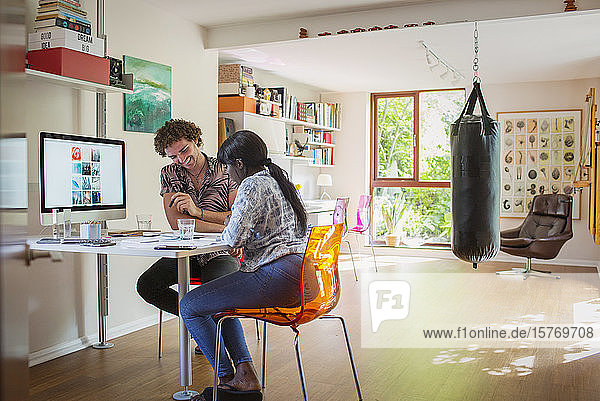 Happy young couple working in home office