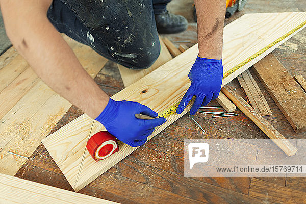 Construction worker measuring and marking floorboard
