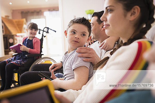 Boy with Down Syndrome watching TV with family