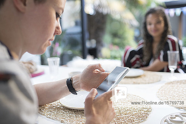Young woman using smart phone at dining table