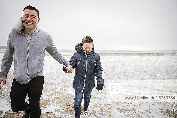 Happy father and son wading in winter ocean surf