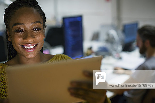 Smiling businesswoman using digital tablet in office