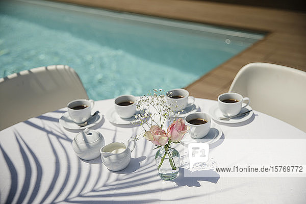 Coffee cups and roses on sunny summer poolside patio table