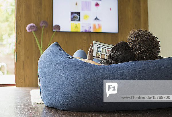 Young couple relaxing streaming photos from digital tablet to TV