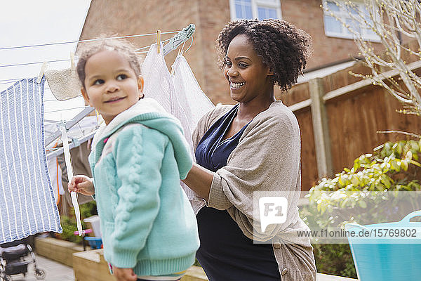 Happy pregnant woman and daughter hanging laundry on clothesline