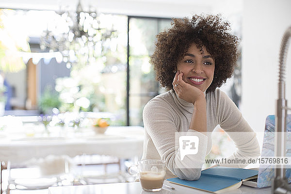 Smiling confident young female freelancer working at laptop
