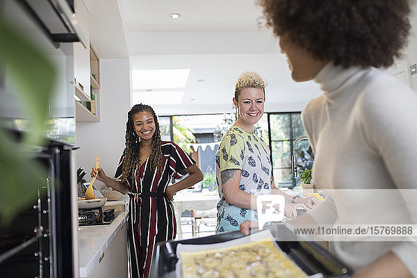 Happy young women friends cooking in kitchen