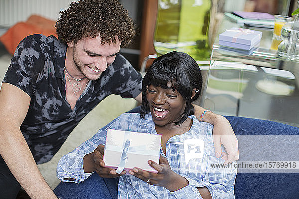 Man giving gift to happy girlfriend