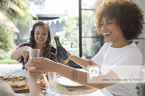 Happy young woman pouring wine for friend at table