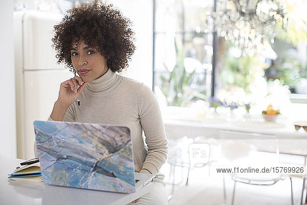 Portrait confident young female freelancer working at laptop