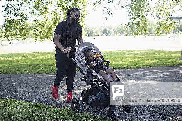 Father pushing toddler son in stroller in park