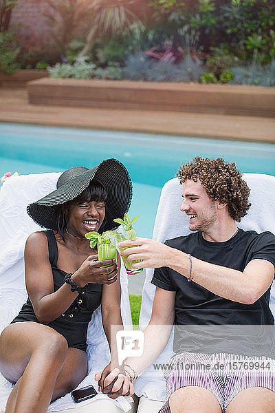 Happy young multiethnic couple drinking cocktails at poolside