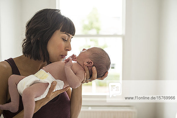 Affectionate mother holding newborn baby son