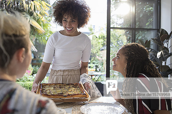 Young woman serving homemade pizza to friends at dining table