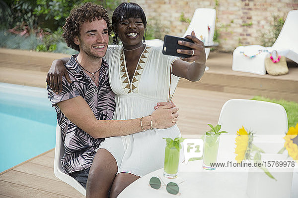 Happy young couple taking selfie with camera phone at poolside