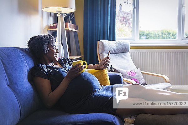 Happy pregnant woman relaxing on sofa with tea and smart phone