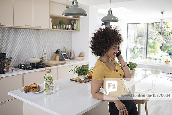 Smiling young woman talking on smart phone in kitchen