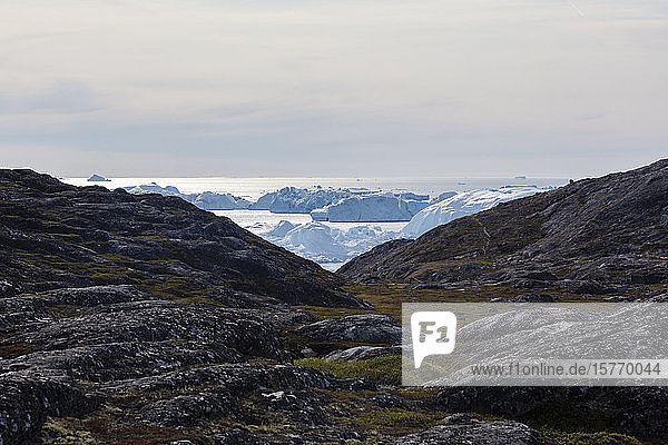 Rocky landscape overlooking icebergs Disko Bay West Greenland