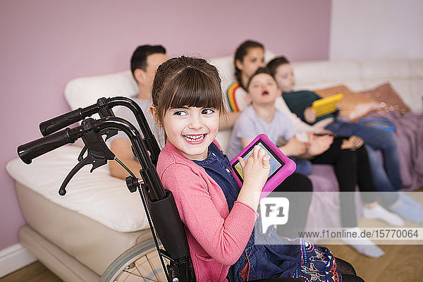 Happy disabled girl in wheelchair using digital tablet