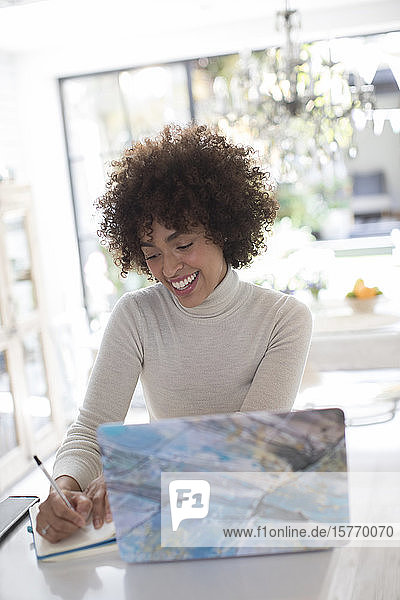 Smiling young female freelancer working at laptop in kitchen