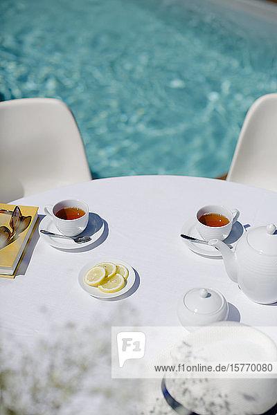 Tea service on sunny summer poolside patio table