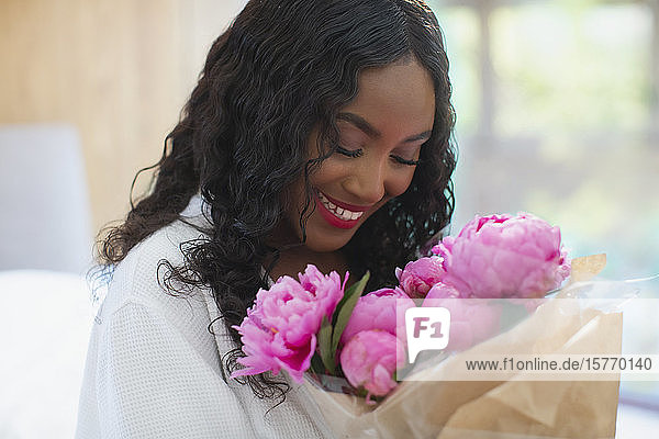 Happy young woman receiving pink peony bouquet