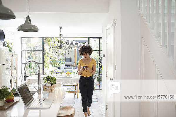 Young woman using smart phone in kitchen