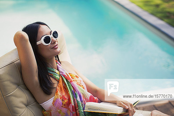 Serene woman relaxing  reading book at summer poolside