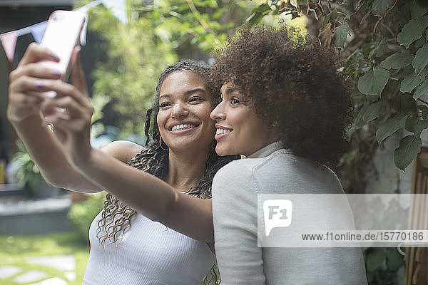 Beautiful young women friends taking selfie with camera phone