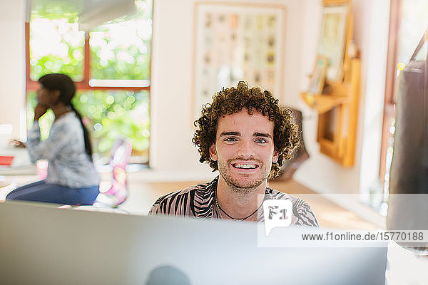 Portrait happy young man working from home at computer