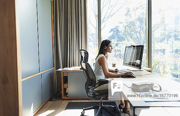 Businesswoman working at computer in home office